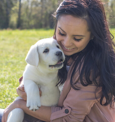 image of woman holding her new white lab puppy and smiling